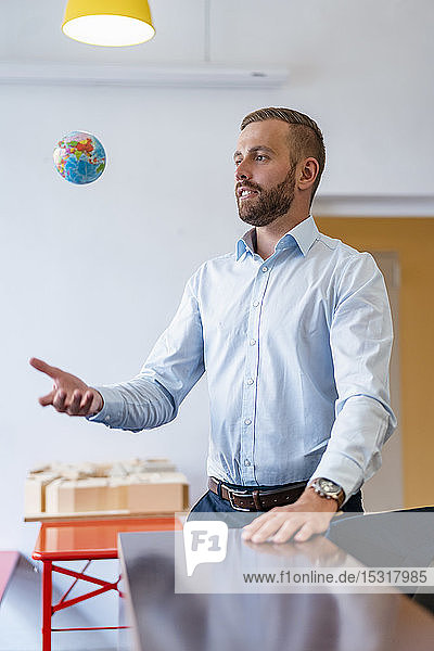 Businessman throwing up miniature globe in office
