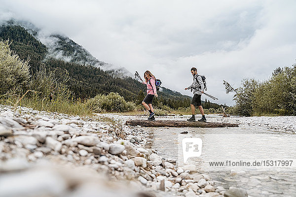 Young couple on a hiking trip crossing river on a log  Vorderriss  Bavaria  Germany