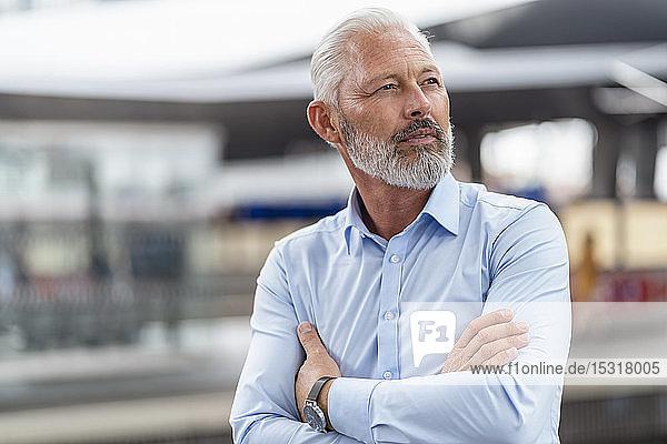 Ein reifer Geschäftsmann am Bahnsteig  der sich umsieht