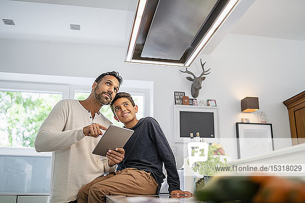 Father and son using tablet in kitchen