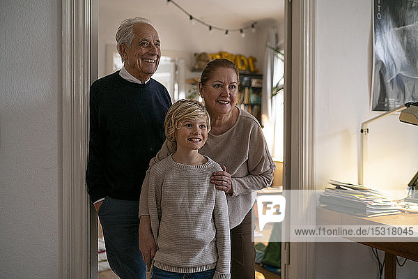 Portrait of happy grandparents with grandson at home
