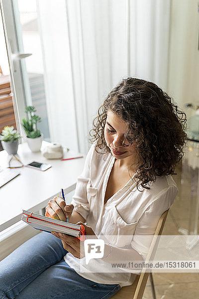 Junge Frau macht sich zu Hause am Schreibtisch Notizen