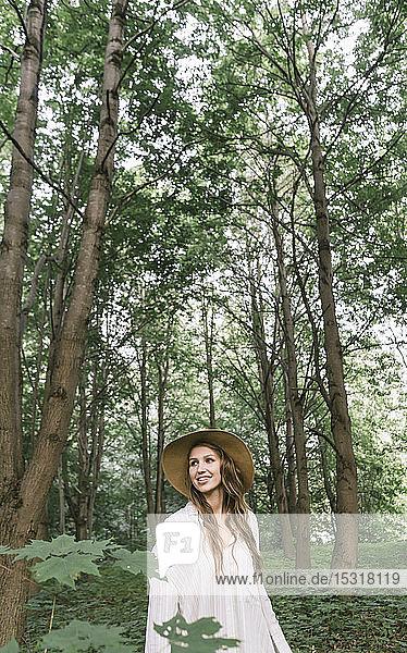 Lächelnde junge Frau mit Hut beim Waldspaziergang