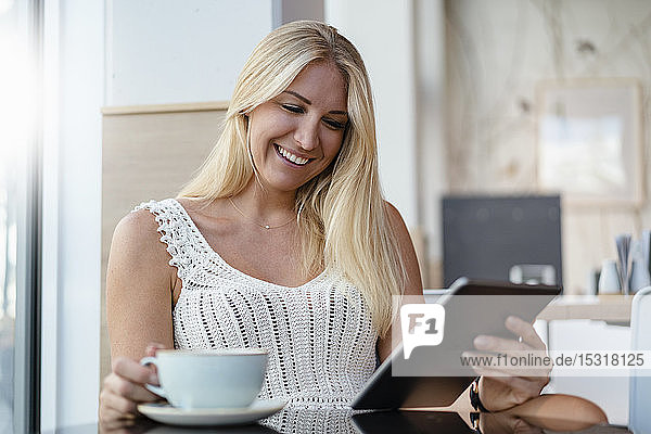 Portrait of smiling blond woman in a cafe using digital tablet