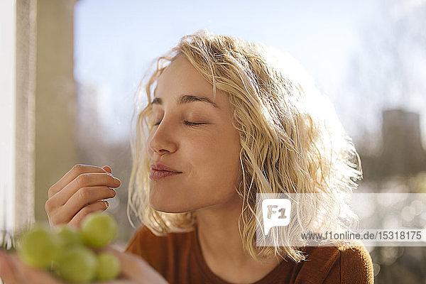 Porträt einer blonden jungen Frau  die grüne Trauben isst