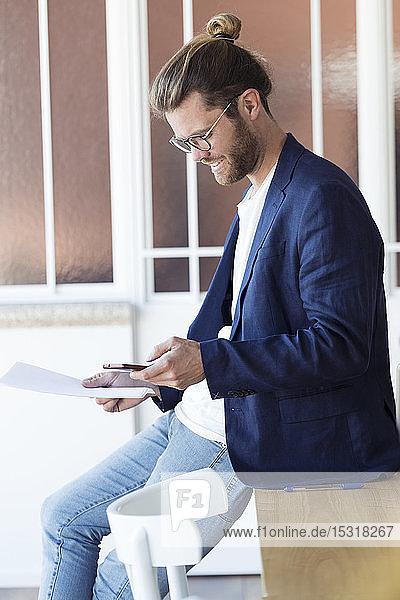 Lächelnder junger Geschäftsmann benutzt Smartphone im Büro