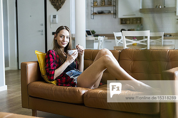 Relaxed young woman eating cereals in living room at home