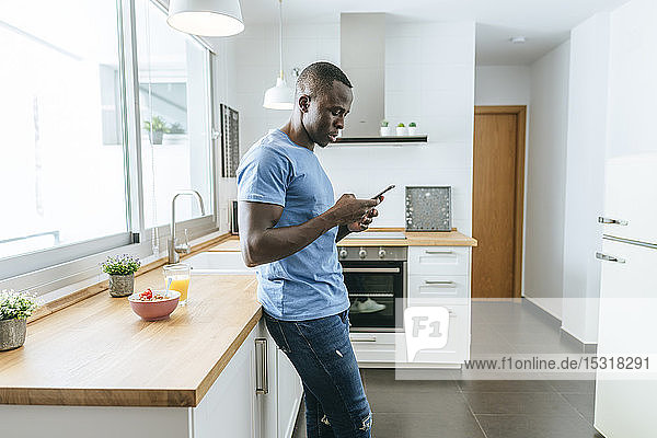 Young man using cell phone in kitchen at home