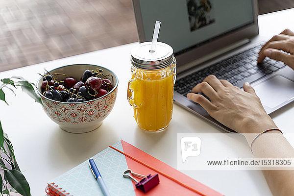 Nahaufnahme einer Frau mit Laptop am Schreibtisch mit Orangensaft und Obst