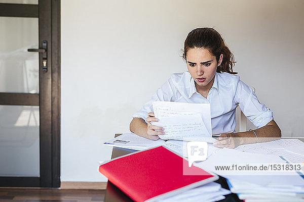 Schockierte Studentin liest Dokument am heimischen Schreibtisch