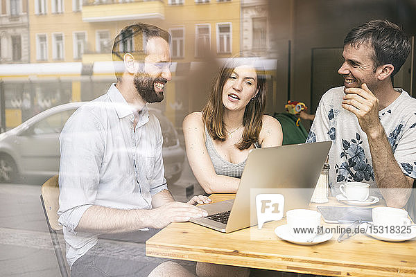 Gruppe von Freunden sitzt mit Laptop in einem Cafe zusammen