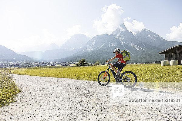 Boy riding e-mountain bike in the mountains