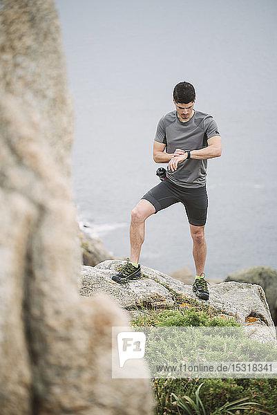 Trail runner standing in coastal landscape looking at his watch  Ferrol  Spain
