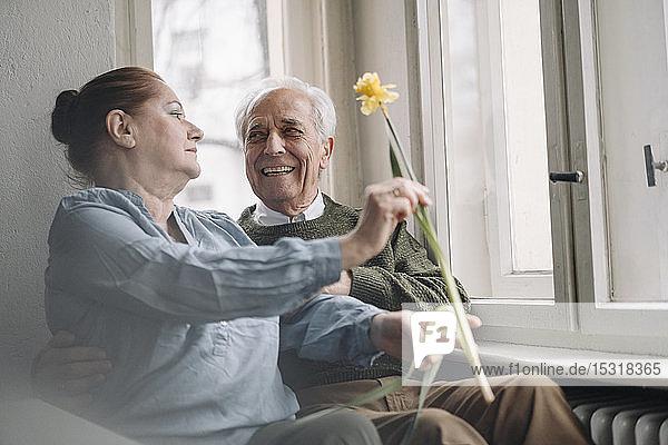 Glückliches älteres Ehepaar mit Blume zu Hause