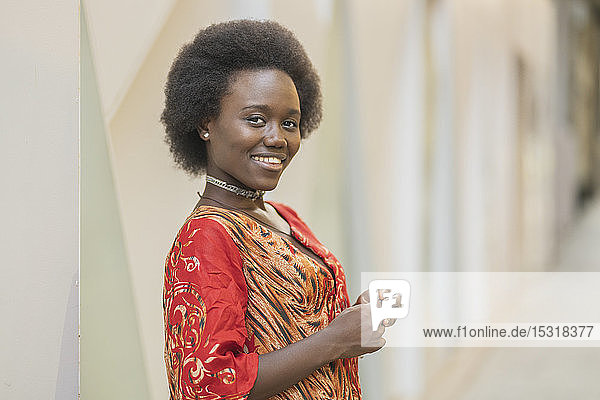 Smiling young woman standing in front of geometric background