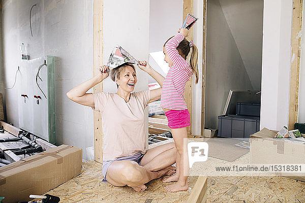 Glückliche Mutter und Tochter mit Papierhüten in einem zu renovierenden Haus