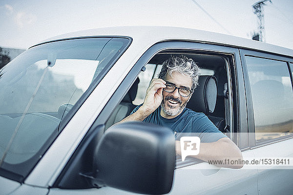 Smiling mature man sitting in his off-road vehicle