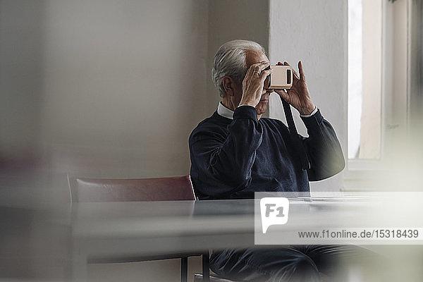 Älterer Mann zu Hause mit VR-Kartonbrille