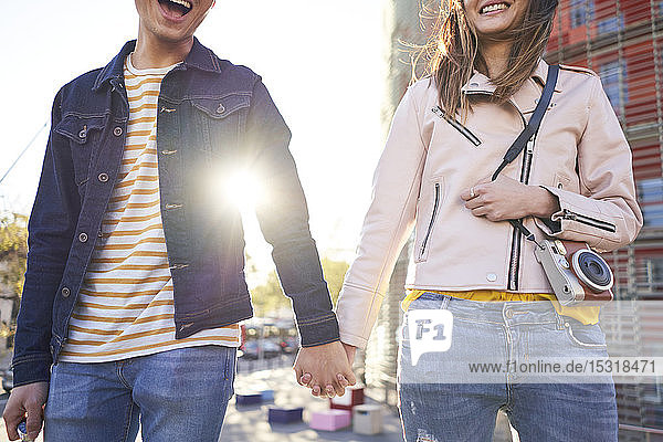 Laughing couple walking hand in hand in the evening  Barcelona  Spain