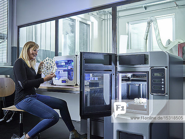 Female technician checking turbine wheel being printed with 3D printer