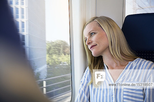 Woman sitting in a train  looking out of window