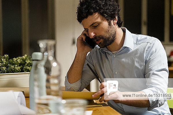 Businessman talking on cell phone at desk in office