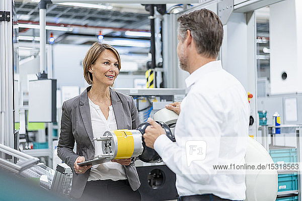 Businesswoman and man talking at assembly robot in a factory
