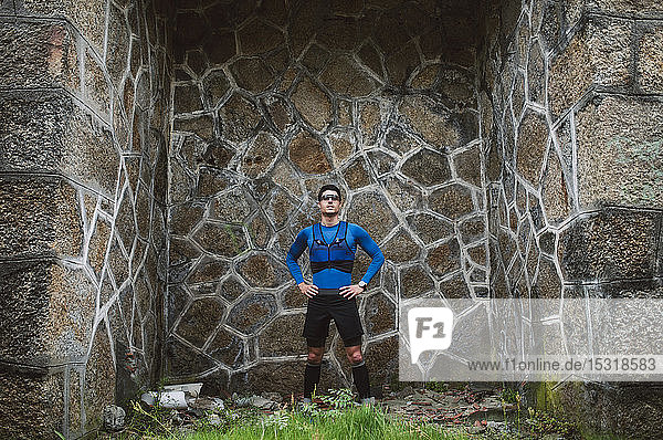 Portrait of trail runner standing at a wall