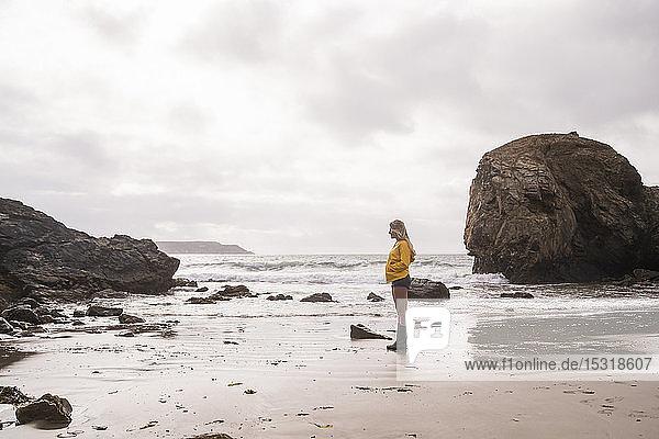 Woman wearing yellow rain jacket standing at rocky beach