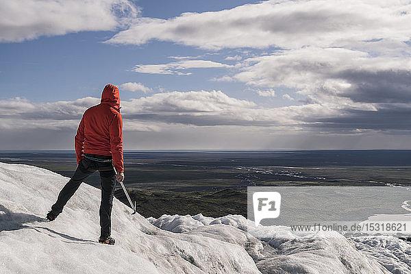 Mature man standing in Skaftafell National Park on Vatnajokull glacier  Iceland  holding ice ax