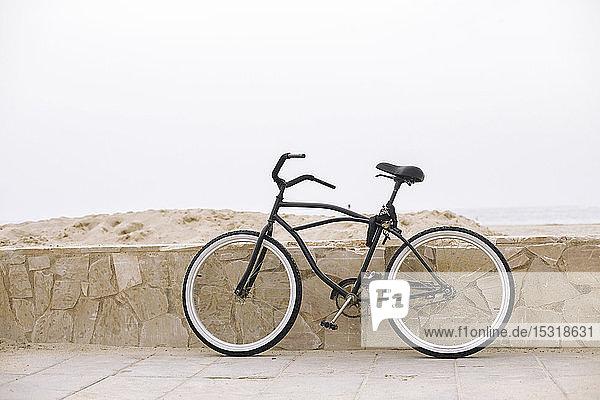 An die Wand gelehntes Fahrrad in Strandnähe  Spanien