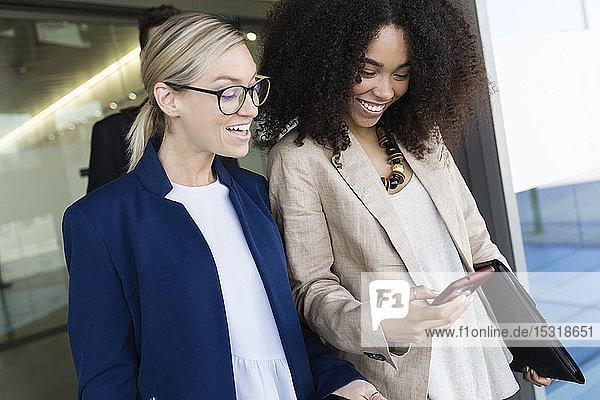 Zwei glückliche junge Geschäftsfrauen schauen auf Smartphone