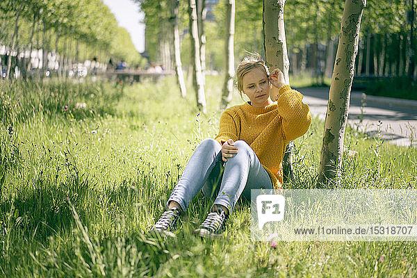 Porträt einer nachdenklichen jungen Frau  die auf einer Wiese sitzt und in die Ferne schaut