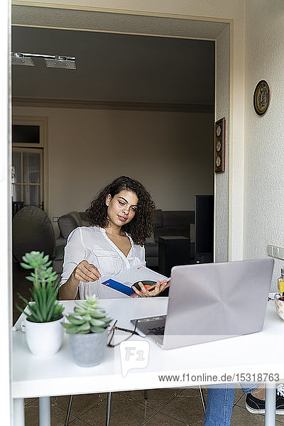 Young woman with notepad and laptop at desk at home