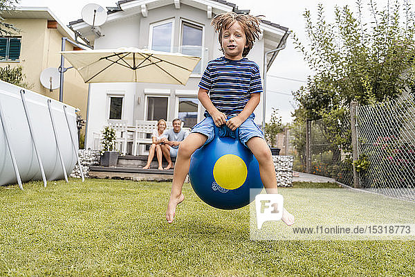 Boy bouncing with hopball in garden with parents in background