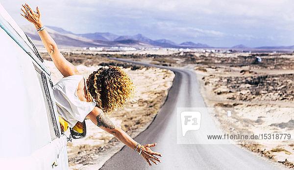 Frau lehnt sich aus dem Fenster eines Lieferwagens  Fuerteventura
