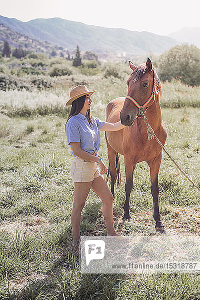 Young woman with a horse on meadow