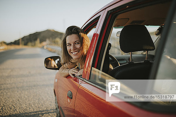 Woman on a road trip looking out of car window