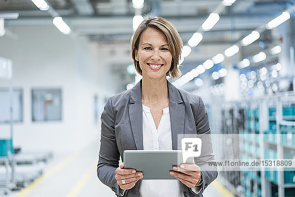 Portrait of smiling businesswoman with tablet in a modern factory