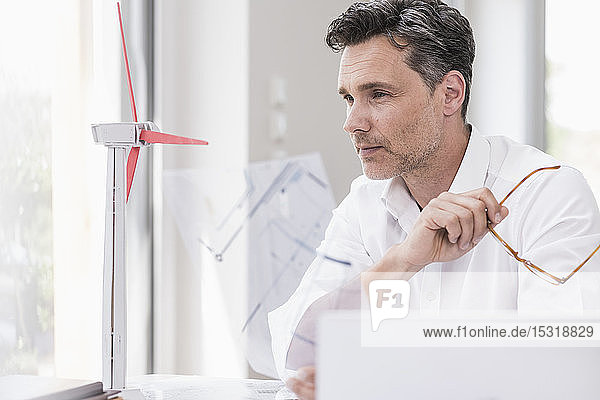 Businessma n sitting in office  using laptop  looking at model of a windwheel