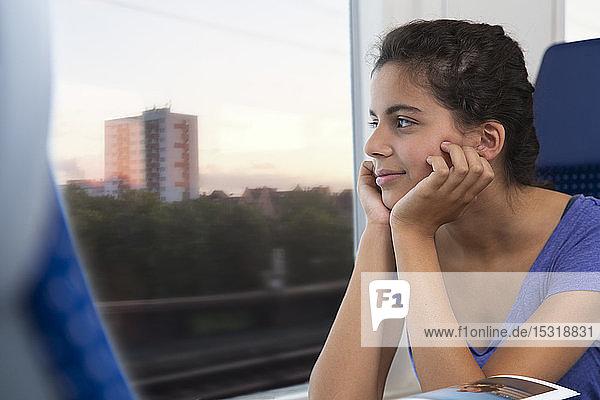Allein im Zug reisendes Mädchen  das aus dem Fenster schaut