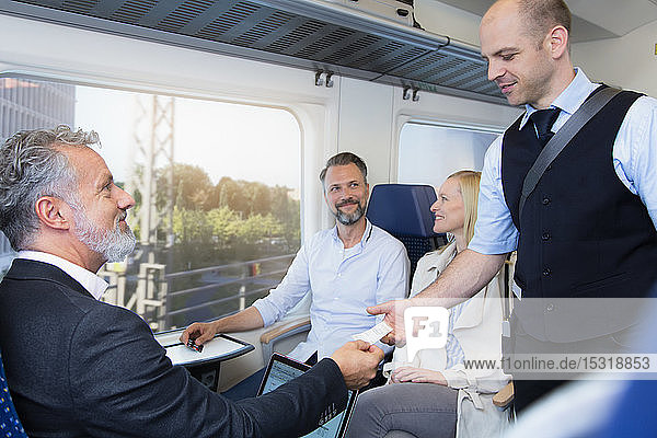 Schaffner bei der Fahrkartenkontrolle von Reisenden in einem Zug