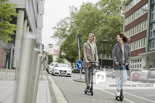 Junge Frauen auf Elektrorollern auf der Straße