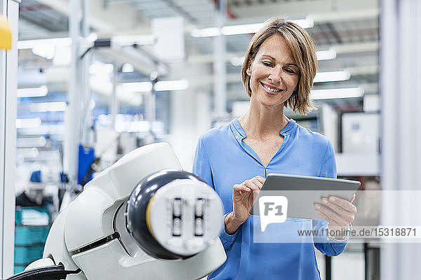 Businesswoman with tablet at assembly robot in a factory