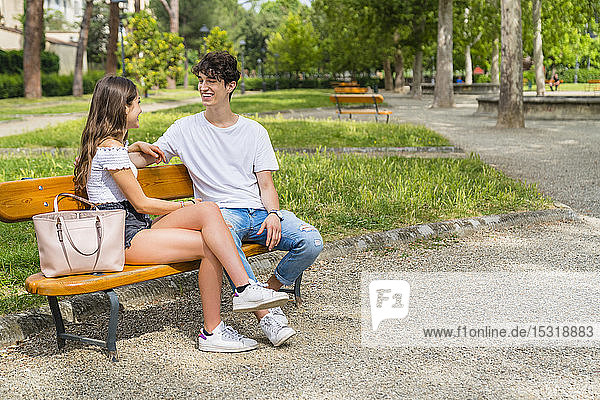 Young couple sitting on a bench and talking to each other in a park