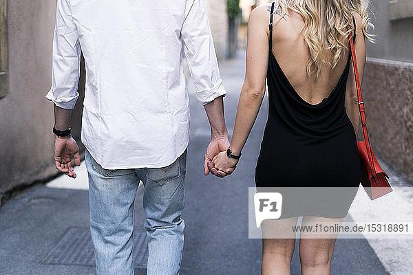 Rückansicht eines verliebten jungen Paares  das in der Stadt Händchen hält