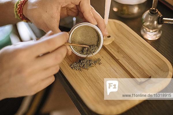 Junger Mann bereitet Marihuana in einem Sieb vor
