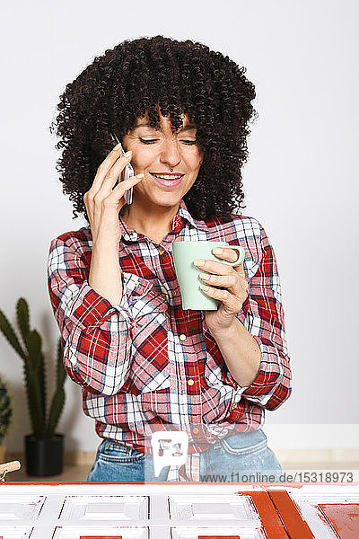 Woman holding cup of coffee at home and using smartphone  painted furniture