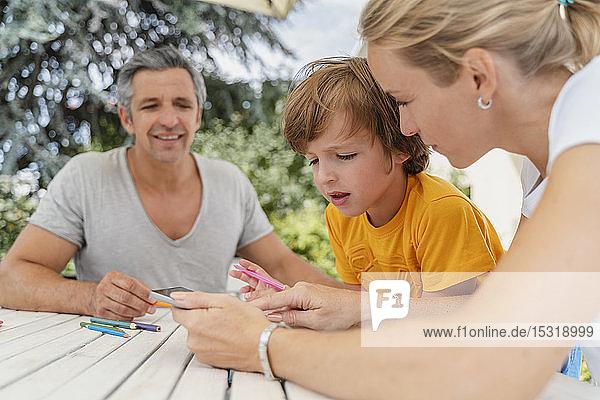 Vater  Mutter und Sohn machen gemeinsam Hausaufgaben auf der Terrasse