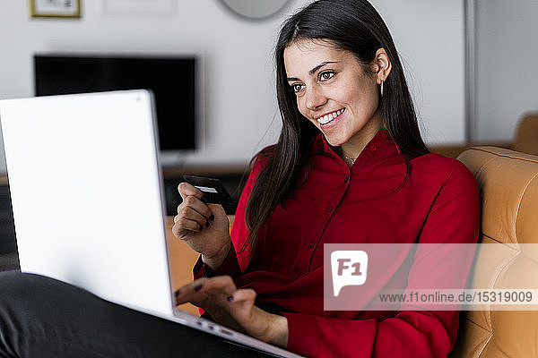 Happy young woman at home shopping online